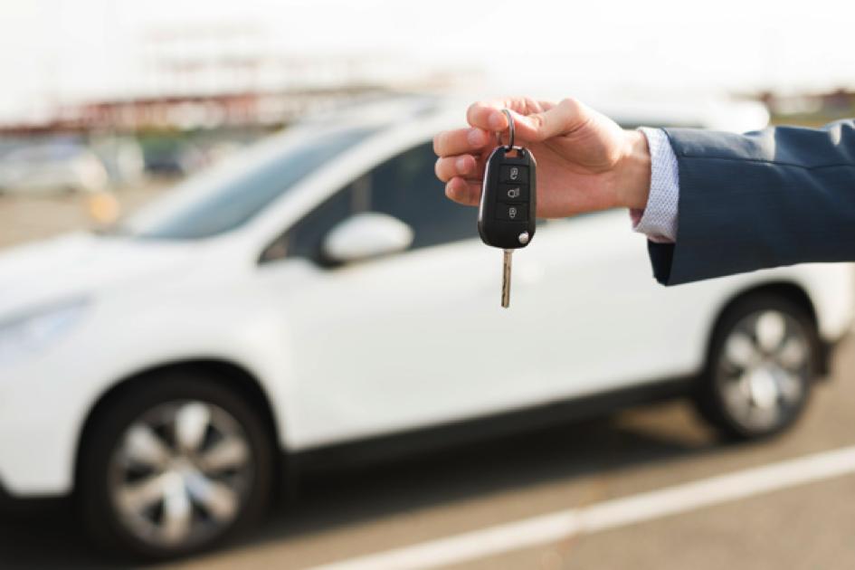 homme qui tient une clé devant une voiture en leasing blanche