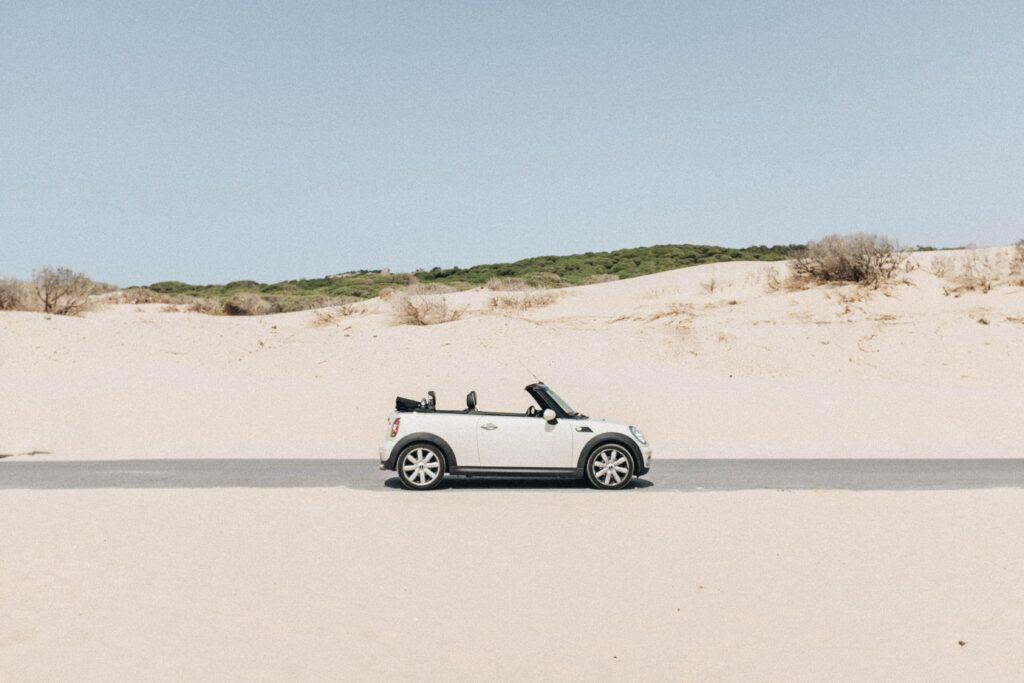 Voiture d'occasion Mini cabriolet blanche en loa sur une petite route de plage