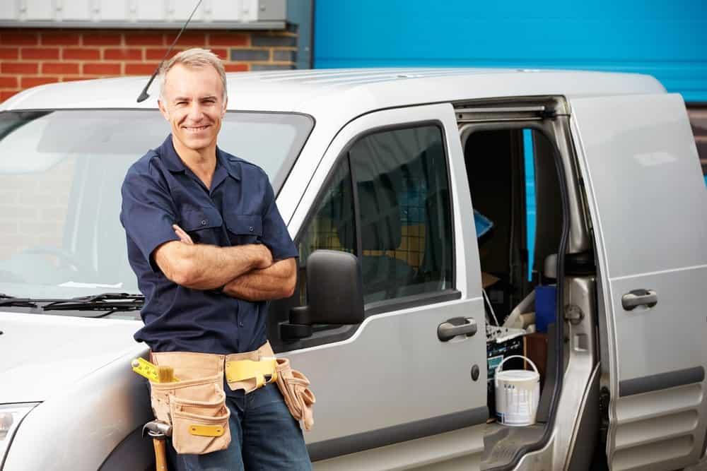 artisan debout devant un véhicule utilitaire en leasing